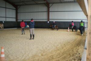des-poneys-montes-par-leurs-cavaliers-lors-un-cours-dans-le-manege-ecuries-nicolas-mergnac.