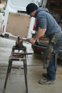 marechal-ferrand-qui-tape-avec-un-marteau-sur-un-morceau-de-metal-rougi-ecuries-nicolas-mergnac